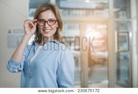Portrait Of Glad Woman Wearing Eyeglasses While Standing In Optical Store. Ophthalmology Concept