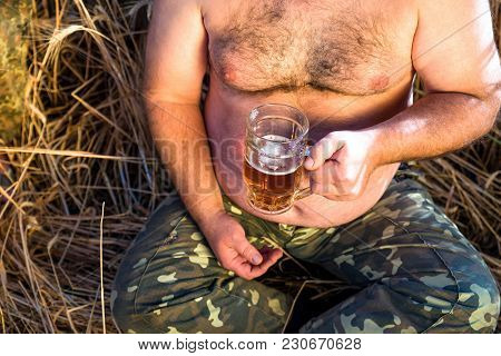 A Glass Of Beer Is Held By A Fat Man In Hands. A Glass Of Beer Near A Large Beer Belly Of A Man, Clo