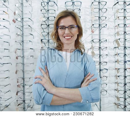 Portrait Of Beaming Female Client Standing In Glasses Shop. Ophthalmology Concept