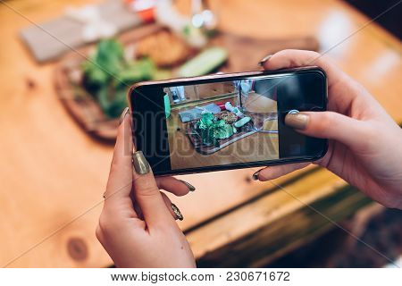 Food Photography For Social Networks. Close-up Image Of Female Hands Holding Phone With Food On Scre