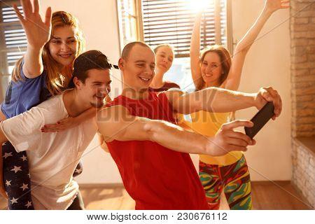 Young smiling dancers group taking selfie in dancing studio