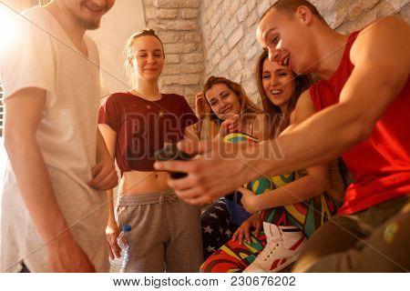 Happy friends in dancing studio looking photos together