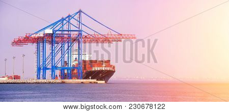 Container Ship In The Port On The Horizon. Port Crane Loads A Container On A Ship. Cargo Transportat