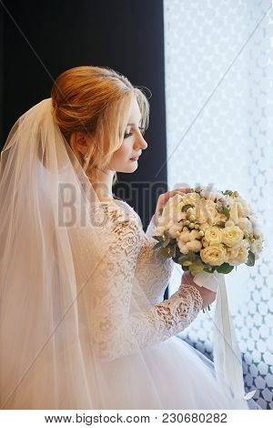 Blonde Bride In A White Wedding Dress And A Long Veil Is Waiting For The Groom And The Beginning Of