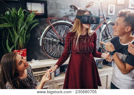 Group Of Cheerful Students Supporting Their Female Friend Playing Funny Game Using Virtual Reality H
