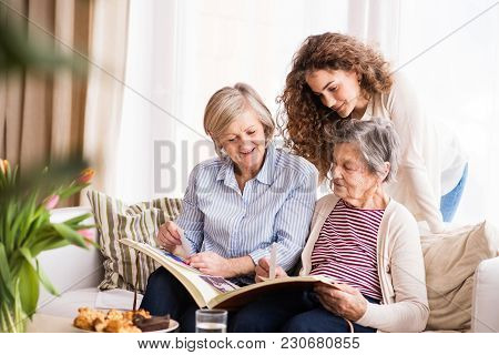A Teenage Girl, Her Mother And Grandmother Looking At Old Photographs At Home. Family And Generation