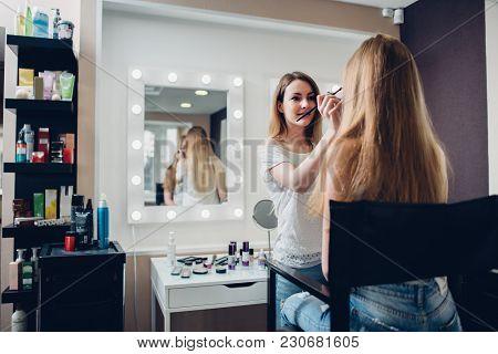 Smiling Female Esthetician Applying Makeup Using Brush To The Female Model In Stylish Beauty Studio.