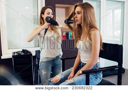 professional hairstylist using hairdryer and round brush to style long fair hair of the female custo