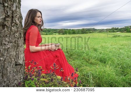 Beautiful Woman, In An Elegant Red Dress, Sitting On A Bench Under A Tree, With A Book And Pocket Wa