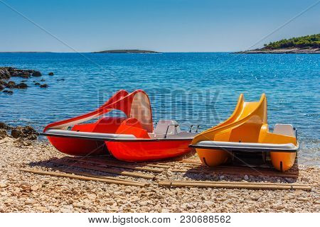 Yellow And Red Pedal Catamaran Boats With Slide On A Sea Coast On A Sunny Day