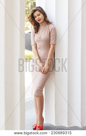 Young Beautiful Woman In A Dress Poses Near Ancient Colons