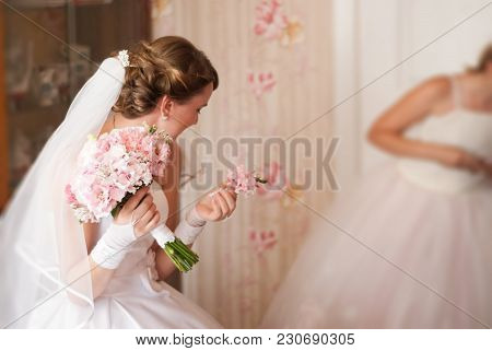 The Bride Is Embarrassed, The Girl In The Wedding Dress Holds A Wedding Bouquet, Without A Face