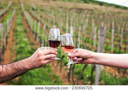 A Man And A Woman Check With Glasses Of Wine. Glasses With Red Wine In The Female And Male Hands. Cl