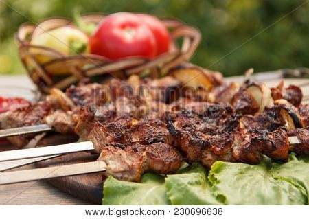 Grilled Pork On Metal Skewers Roasted On The Grill And Lettuce Leaves On Wooden Chopping Board With