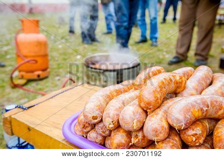 Pile Of Fresh Uncooked Juicy Sausages Waiting To Be Cooked On Barbecue Plate.