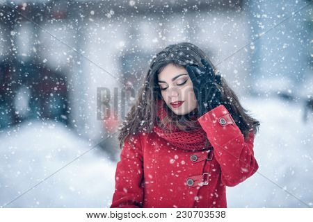 Winter Portrait Of Young Beautiful Brunette Woman Wearing Knitted Snood And Red Coat Covered In Snow