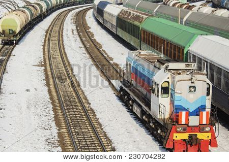 Locomotive And A Lot Of Freight Cars. In Winter