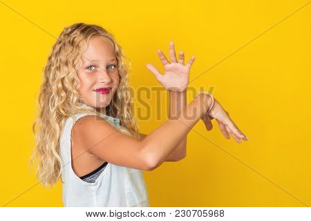 Handsome Young Girl Posing On The Yellow Background.