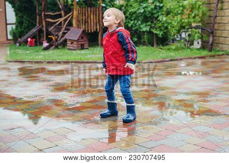 Happy Boy Jumping In Puddles After Rain.