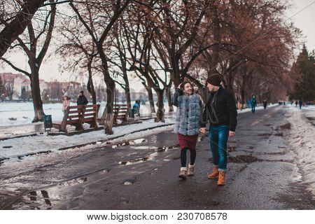 Romantic couple walking on the quay in winter under the snow poster