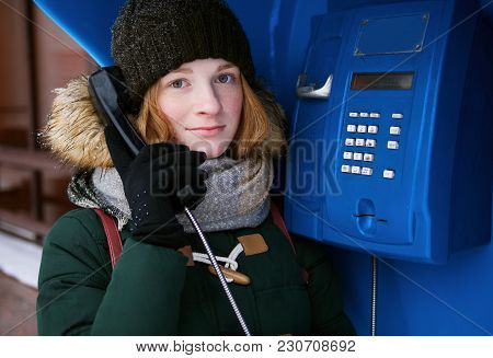 Beautiful Young Redhead Girl In Cold Season Outfit Using Street Blue Payphone.