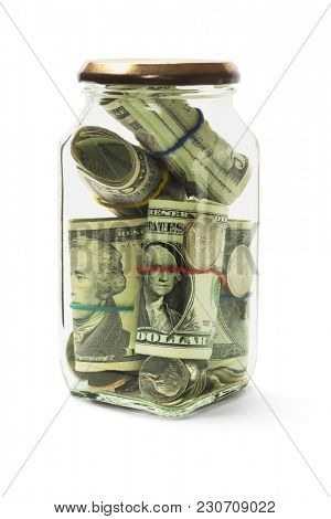 US Dollars Bills and Coins in Glass Jar on White Background