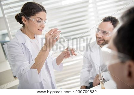 Important Test. Pretty Inspired Dark-haired Ecologist Smiling And Holding Test Tubes And Her Colleag