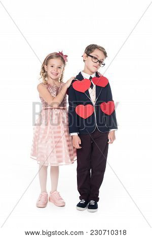 Happy Little Girl Embracing Upset Boy Tied With Rope And Red Hearts Isolated On White