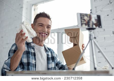 In High Spirits. Good-looking Glad Young Well-built Man Smiling And Holding His Gift While Making A