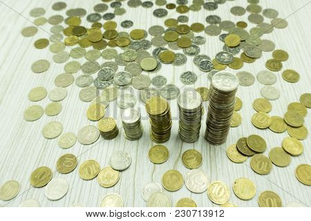 Macro Close Up View Of A Stack Of Coins On A Pile Of Banknotes. Currencies Or Money Are Recognized S