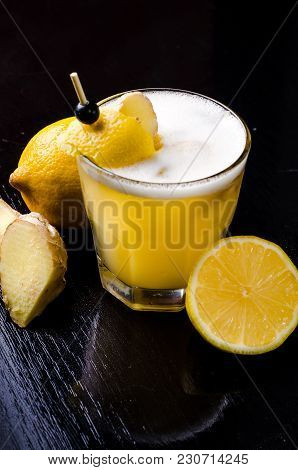Yellow Drink With Lime, Ginger, Honey And Ice. Organic Strong Cocktail In A Glass With Decoration Ro