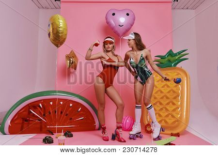 On The Way To Perfect Shape. Full Length Of Two Playful Young Women In Swimwear Exercising While Sta