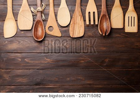 Various cooking utensils over wooden kitchen table. Top view with space for your recipe