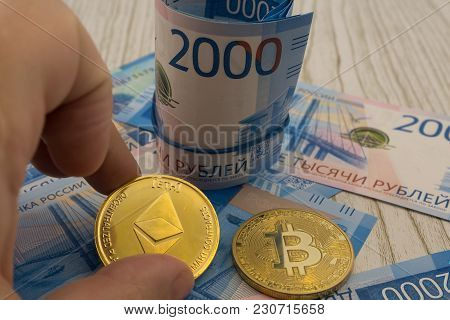 Hand Holding A Single Ether Or Ethereum Coin Over Bitcoins On Gold Background To Illustrate Blockcha