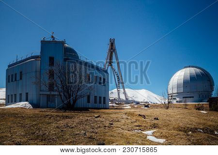 Astrophysical Observatory In Mountains On Blue Sky Background At Sunny Day.