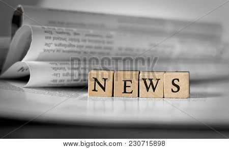 Newspaper And News Sign On Wooden Blocks With Selective Focus And Defocused Background.