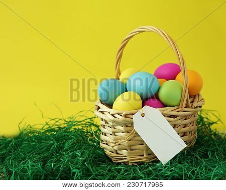 Colorful Easter Eggs Basket On Green Grass Greeting Card With White Blank Paper Label Tag For Messag