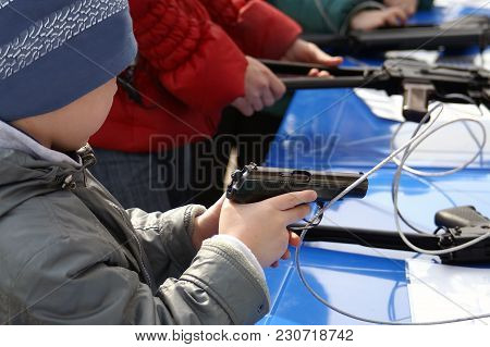 A Kid Holding A Gun Tethered With Metal Cable In A Shooting Gallery