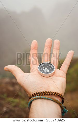 Hand With Compass In The Misty Mountain Terrain.