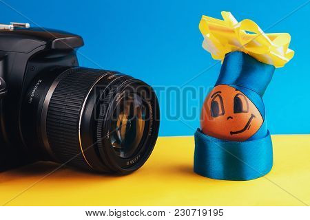 Brown, Positive Egg In Clothes And A Hat With A Bow Posing In Front Of The Camera.on Blue-yellow Bac