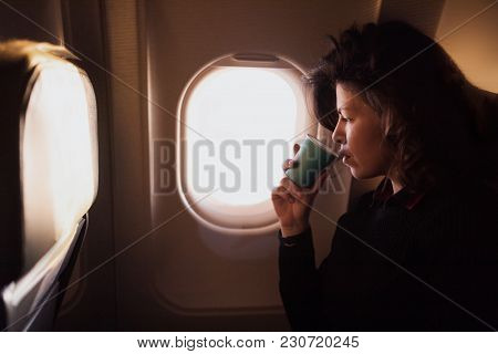 Young Caucasian  Woman Drinking Coffee  Inside Airplane Sitting On Passenger Seat Near Window. Happy