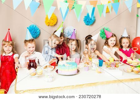 Kids Are Celebrating Birthday. Children Near The Table, Friends Are Exciting In The Hours Of Sweet P