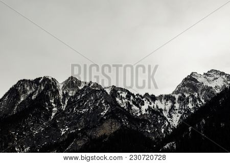 Snow Covered Alpine Peak On A Gloomy Winter Day With Heavy Cloud Cover In A Bleak Cold Alpine Austri