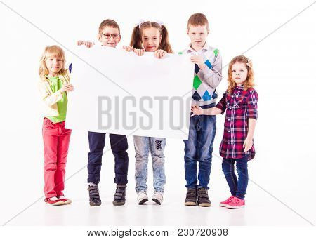Group Of Children Isolated On White Background Are Holding A White Poster With Copyspace.