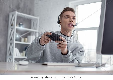 Having Fun. Handsome Determined Fair-haired Teenager Looking Attentively And Wearing Headphones Whil