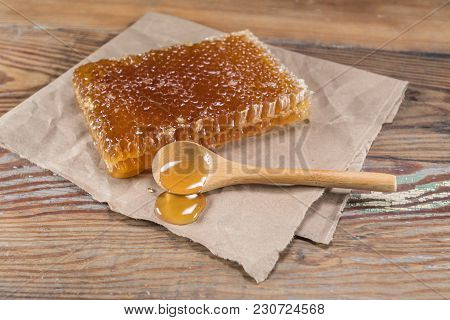Rectangle Honey Comb And Wooden Spoon Of Honey