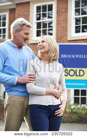 Mature Couple Standing Outside New Home With Sold Sign