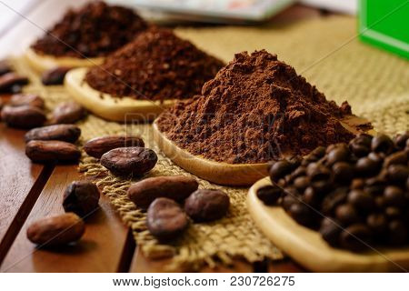 Cacao Powder, Cocoa Nibs, And Coffee Beans On Wooden Plates On Burlap Background