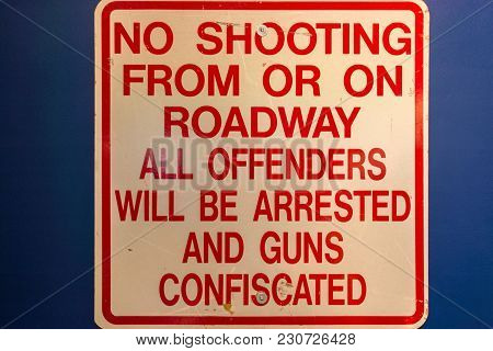 Road Sign: No Shooting From Or On Roadway. All Offenders Will Be Arrested And Guns Confiscated.