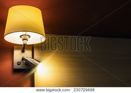 Lamp Over The Bed In The Room Or Hotel Room Against The Backdrop Of Furniture. The Interior Of The R